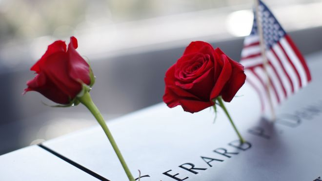 A pair of roses and an American flag sit on top of a September 11, 2001 memorial panel